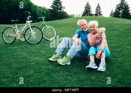 happy senior couple sits on the grass, enjoying the rest after riding bicycles. Bicycles stand next to them. Active rest old people, - Stock Photo