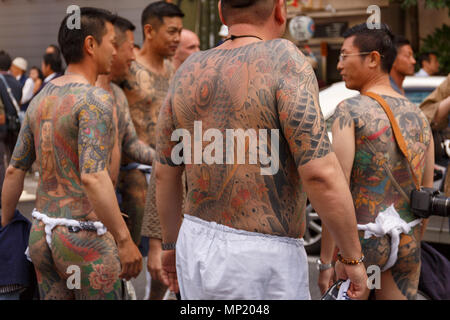 Participants showing their full body tattooed, possibly members of the Japanese mafia or Yakuza, attend the Sanja Matsuri in Asakusa district on May 20, 2018, Tokyo, Japan. The Sanja Matsuri is one of the largest Shinto festivals in Tokyo, and it is held in Tokyo's Asakusa district for three days around the third weekend of May. Large groups of people dressed up traditional clothes carry Mikoshi (sacred portable shrines) between the streets near to Sensoji Temple to bring blessing and fortune tothe inhabitants of the neighboring community at Asakusa - Stock Photo