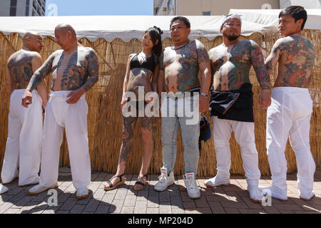 Participants showing their full body tattooed, possibly members of the Japanese mafia or Yakuza, attend the Sanja Matsuri in Asakusa district on May 20, 2018, Tokyo, Japan. The Sanja Matsuri is one of the largest Shinto festivals in Tokyo, and it is held in Tokyo's Asakusa district for three days around the third weekend of May. Large groups of people dressed up traditional clothes carry Mikoshi (sacred portable shrines) between the streets near to Sensoji Temple to bring blessing and fortune tothe inhabitants of the neighboring community at Asakusa. - Stock Photo