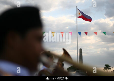 Manila, Philippines. 20th May 2018. The Philippine flag raised on Rizal park, Manila. The Department of Tourism held a Flores de Mayo festival at the Rizal Park in Manila. The fiesta themed celebration was a showcase of Filipino games and native dances performed around the national park, Sunday afternoon. Credit: SOPA Images Limited/Alamy Live News - Stock Photo