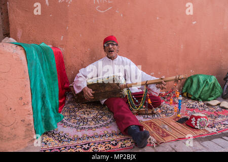 Musician plays on the streets of the souk in the medina of Marrakech, Morocco. - Stock Photo