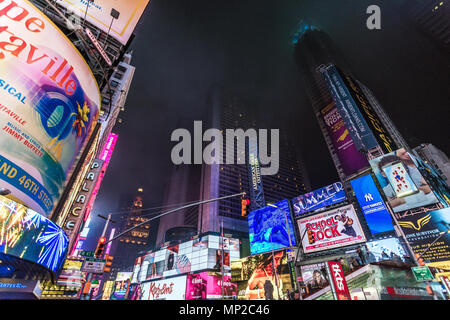 New York, US - March 30, 2018: View of people visiting the famous Times Square in New York on a foggy night - Stock Photo