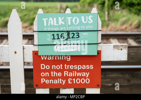 Sign of The Samaritans attached to railway level crossing in the UK. - Stock Photo