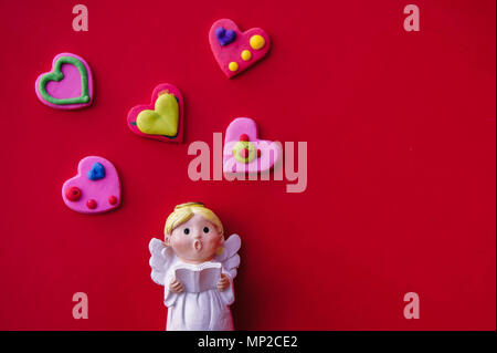 Cupid doll and heart-shaped on red background - Stock Photo