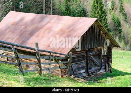 Old-fashioned wooden barn on the outskirts of the forest. Among the Carpathian mountains in Ukraine. Outdoors. Close-up. - Stock Photo