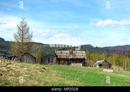 Old-fashioned wooden destroyed outbuildings on the outskirts of the forest. Among the Carpathian mountains in Ukraine. Outdoors. Close-up. - Stock Photo