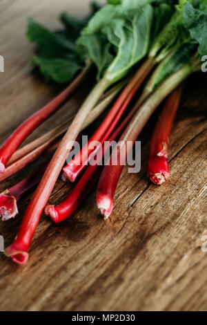 Red rhubarb stalks with large green leaves freshly harvested from the garden or bought on farmer market. Wooden background, close up, vertical. - Stock Photo