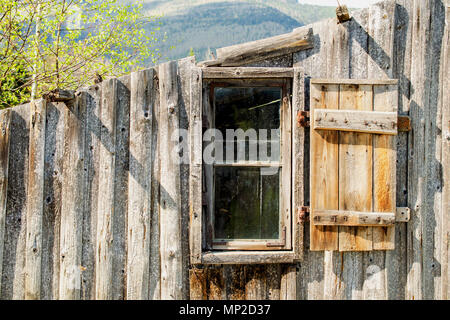 Old-fashioned wooden destroyed outbuilding on the outskirts of the forest. Among the Carpathian mountains in Ukraine. Outdoors. Close-up. - Stock Photo