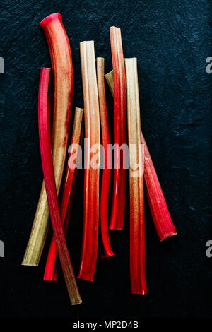 Red rhubarb stalks on black background. Minimalistic, view from above. - Stock Photo