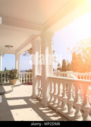 Large white balcony with columns and views of the Park and the sea on a Sunny day. - Stock Photo