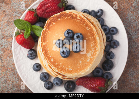 Close-up delicious pancakes, with fresh blueberries, strawberries and maple syrup on a rusty background. - Stock Photo