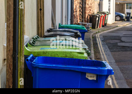 Row of large colourful domestic dustbins in a back street behind houses. Teignmouth, Devon. Feb 2018. - Stock Photo