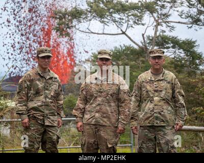 The Hawaii National Guard Joint Task Force 5-0 command team, Col. Neal Mitsuyoshi, Brig. Gen. Kenneth Hara and Col. David Williamson pose in front of a massive lava fountain spewing out from fissure 17 caused by the eruption of the Kilauea volcano May 18, 2018 in Pahoa, Hawaii. - Stock Photo