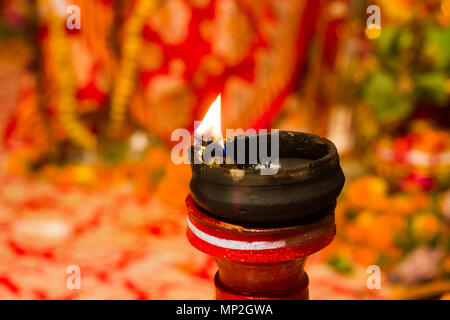 lit clay lamp on top of a clay stand or worship idol durgapuja india diwali - Stock Photo