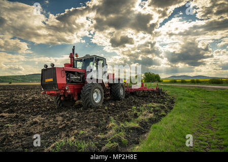Farmer in tractor preparing land with seedbed cultivator. - Stock Photo