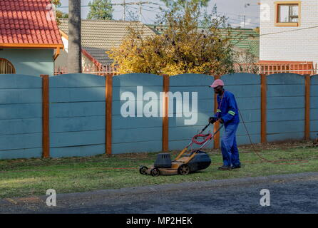 Johannesburg, South Africa - unidentified black man does unskilled gardening work at a private residence in the city image with copy space - Stock Photo