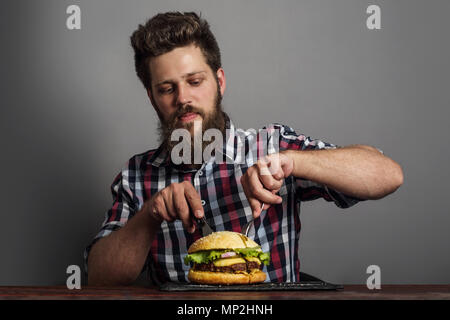 Man eating fresh self made burger close up - Stock Photo