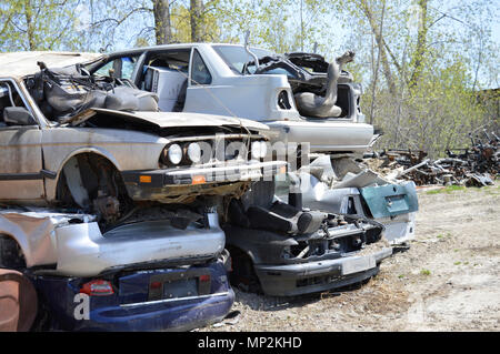 Pile of broken cars sitting on top of each other in a scrap yard - Stock Photo