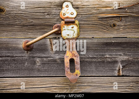 Close up old rusty handle and hinge on grey wooden texture - Stock Photo