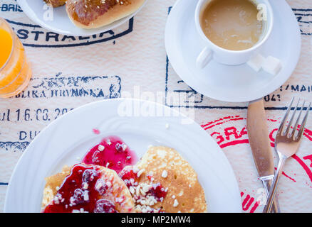 Breakfast including classic pancakes with raspberry jam, coffee with milk and pastries. Good morning. Top view. - Stock Photo