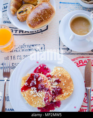 Breakfast including classic pancakes with raspberry jam, coffee with milk, fruits and pastries. Good morning. Top view. - Stock Photo
