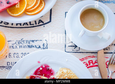 Breakfast including classic pancakes with raspberry jam, coffee with milk and fruits. Good morning. Top view. - Stock Photo