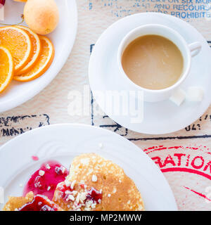 Breakfast including classic pancakes with raspberry jam, fruits and coffee with milk. Good morning. Top view. Square. - Stock Photo