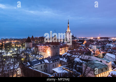 Twilight over the Tallinn old town cityscape with the Saint Olaf church and the medieval fortified wall in Estonia capital city. - Stock Photo