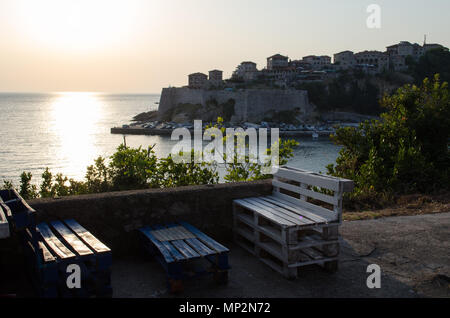 Cozy bar with the beautiful sunset view on sea and Stadi Grad - old town of Ulcinj at twilight scene. Coast of Adriatic sea. Montenegro. - Stock Photo