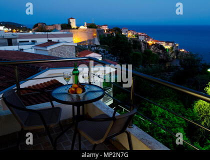 Table with bottle of white wine, two glasses and fruits on balcony with beautiful view on sea and Stari Grad at twilight scene. Romantic celebration o - Stock Photo