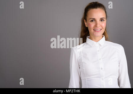 Young beautiful businesswoman against gray background - Stock Photo