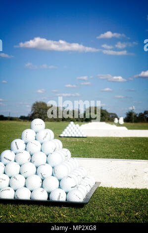 Golf balls neatly arranged at a practice range. - Stock Photo