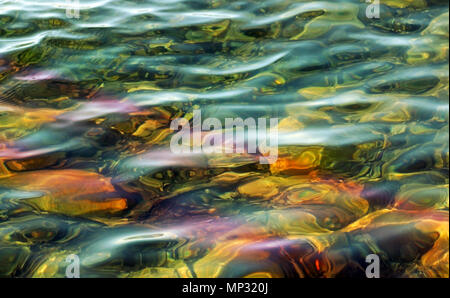 Beautiful waters with soft ripples moving along surface.   Rocks can be seen on shallow bottom below - Stock Photo