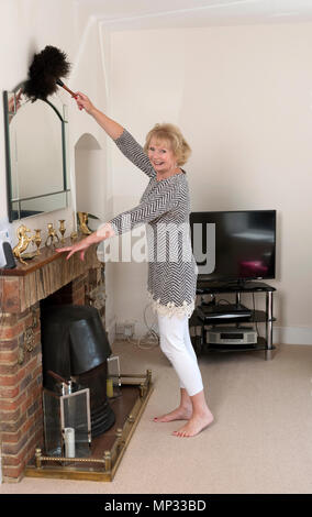 House Move; Woman using an Ostrich feather duster to dust  a wall mounted mirror in her home - Stock Photo