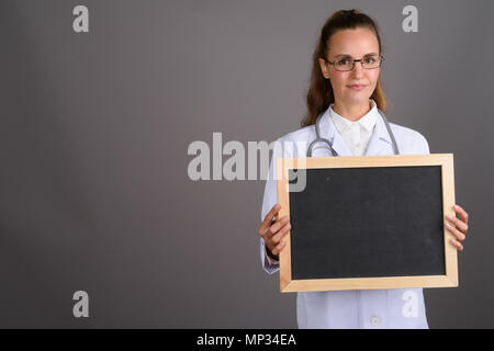 Young beautiful woman doctor against gray background - Stock Photo