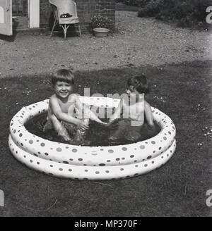1961, historical, outdoors in a garden and two young boys in swimming truncs playing and having fun together in a small round paddling pool, England, UK. - Stock Photo