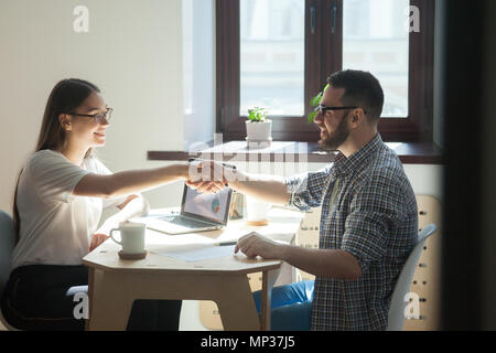 Female employer shaking hand of male job applicant - Stock Photo