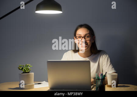 Happy freelancer smiling to camera posing at office desk - Stock Photo
