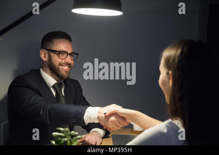 Happy male shaking hand of female job applicant during interview - Stock Photo