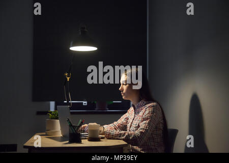 Tired female browsing information at laptop working late hours - Stock Photo