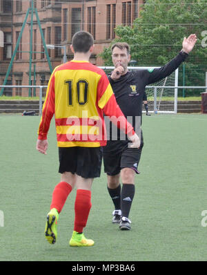 GLASGOW, SCOTLAND - JUNE 8th 2014: A referee blows his whistle while a player looks on. - Stock Photo