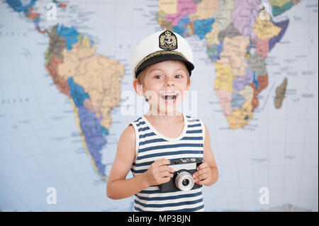 cute laughing boy in captain's hat and vintage film camera in hands on world map background - Stock Photo