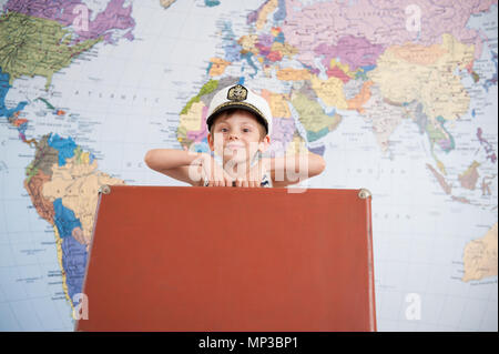 happy smiling little kid in captain hat lifting travel suitcase on world map background in summer vacation - Stock Photo