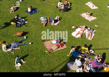 People relaxing and enjoying the afternoon sunshine at Reuilly Paul Permin park in Paris, France. - Stock Photo