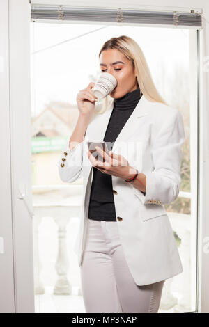 Image of cheerful young business woman in office  chatting by mobile phone and drinking coffee while standing next to the window in the office. - Stock Photo