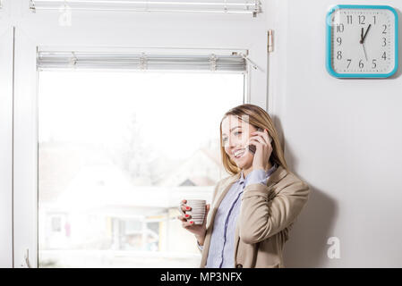 Coffee break. Young smiling businesswoman standing in office  and talking on phone. Business, education, lifestyle concept - Stock Photo