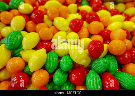 Closeup photo of colorful candies, fruits in red, orange and green color - Stock Photo