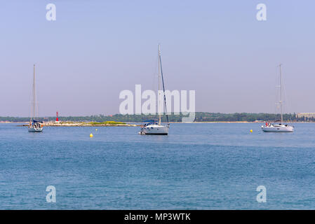 Yachts anchored in bay, sailing boats, small island with red lighthouse in background - Stock Photo