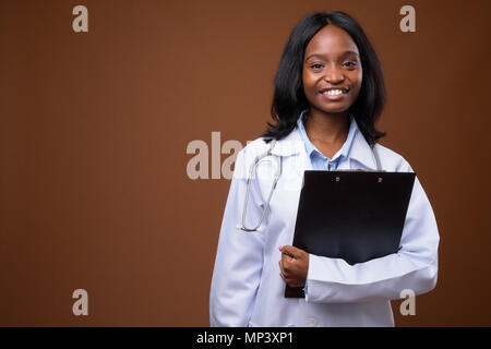 Young beautiful African Zulu woman doctor against brown backgrou - Stock Photo