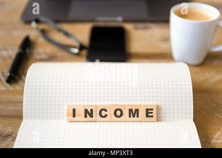 Closeup on notebook over wood table background, focus on wooden blocks with letters making INCOME word. Business concept image. - Stock Photo